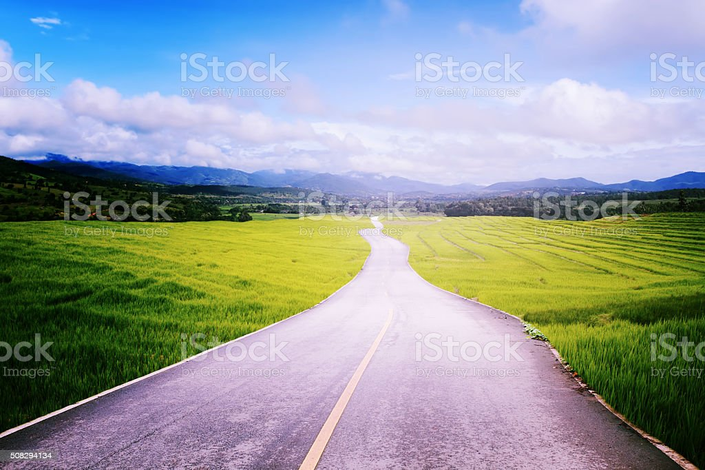 Asphalt road with field in countryside along to blue sky. stock photo