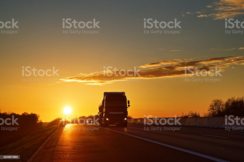 Asphalt road with oncoming truck at sunset stock photo