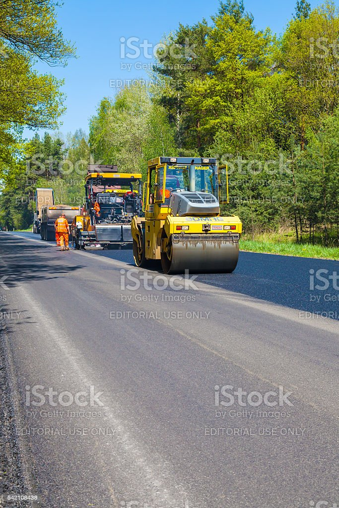 Asphalt spreading machine and vibration roller  at pavement road works. stock photo