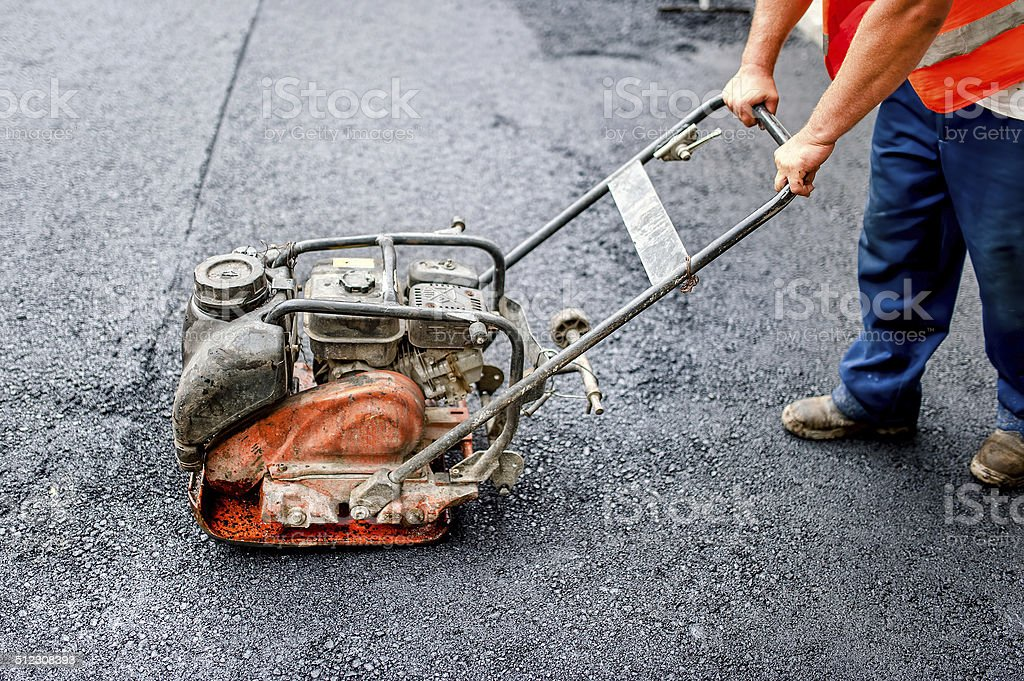 asphalt worker in construction site with manual compactor plate stock photo