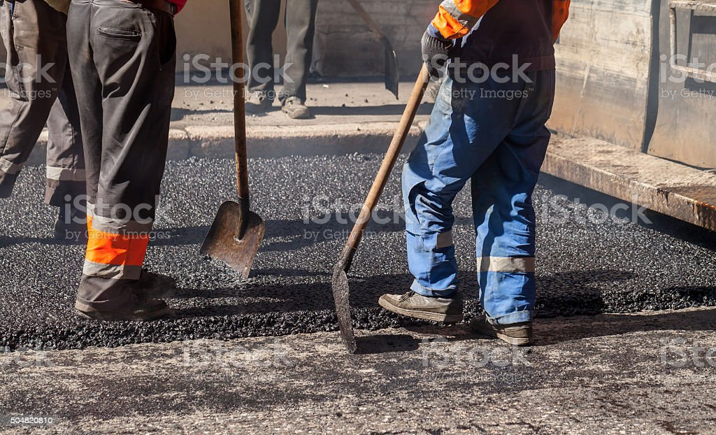 Asphalting in progress, workers in uniform stock photo