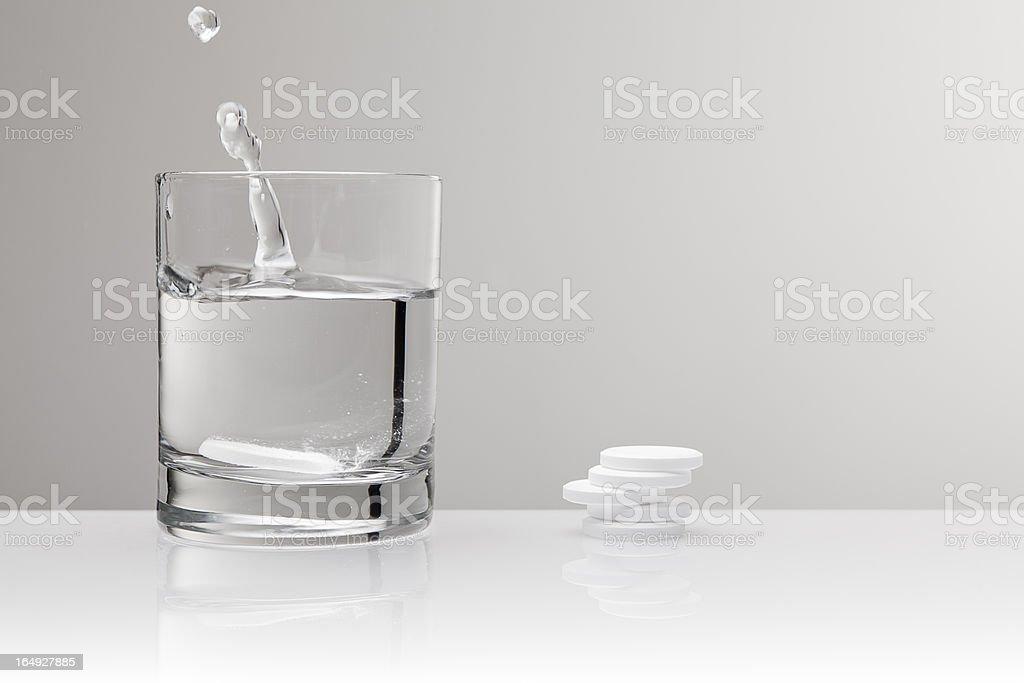Aspirin paracetamol pill splashing into glass of water royalty-free stock photo