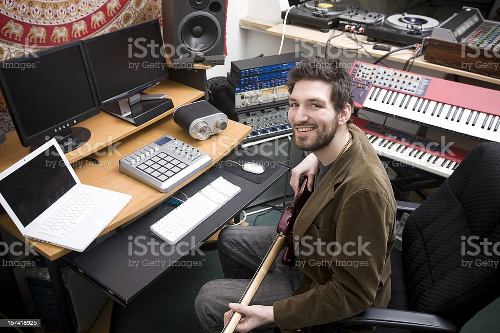 Aspiring Young Male Musician in Studio with Guitar, Computers, Keyboards stock photo