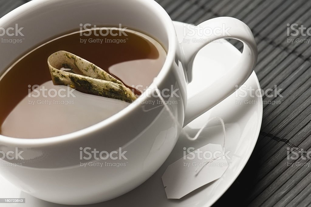 Assam black tea and teabag in white cup and saucer stock photo