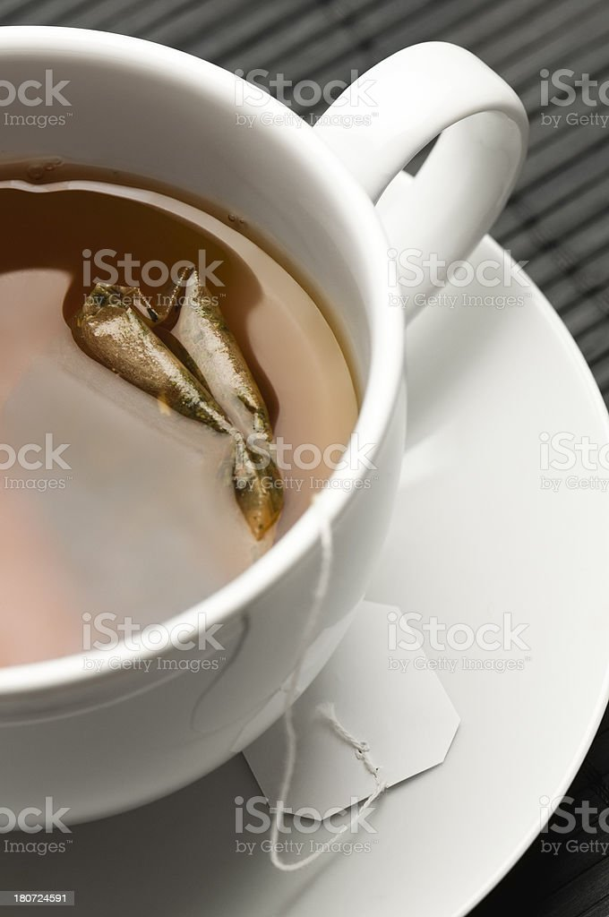 Assam black tea and teabag in white cup and saucer royalty-free stock photo