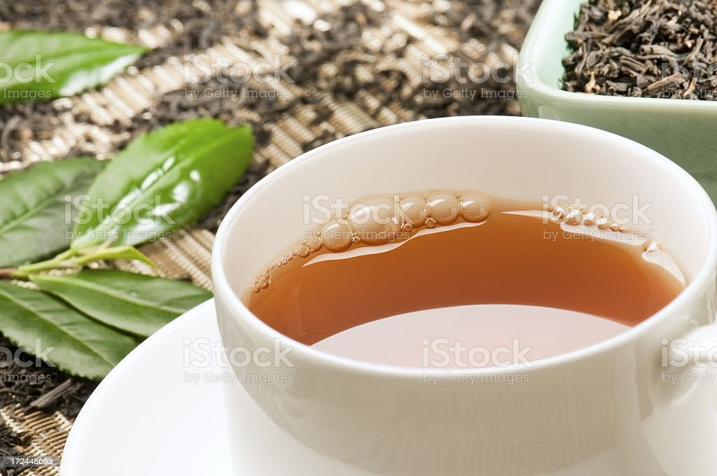 Assam tea and tea leaves in white cup and saucer royalty-free stock photo