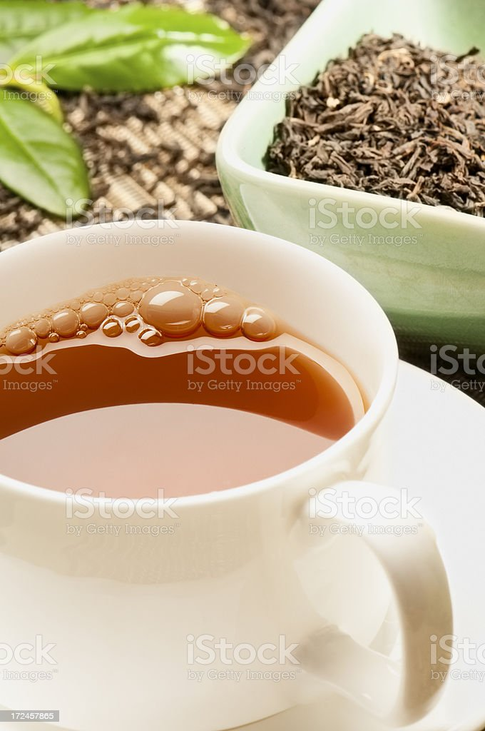 Assam tea and tea leaves in white cup and saucer stock photo