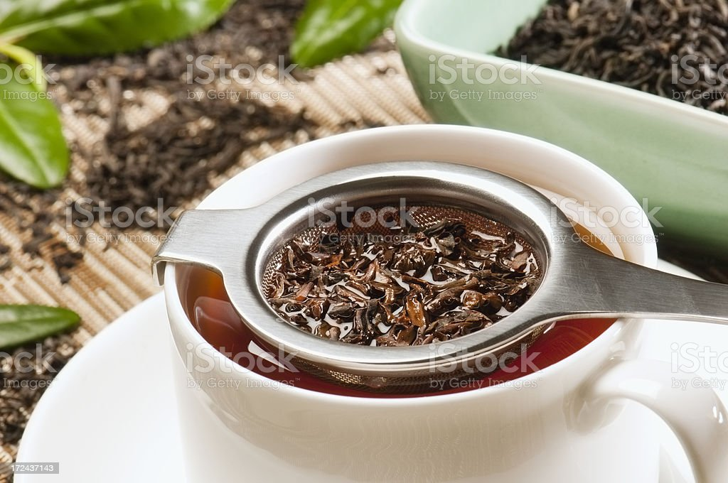 Assam tea leaves straining in diffuser over cup and saucer stock photo