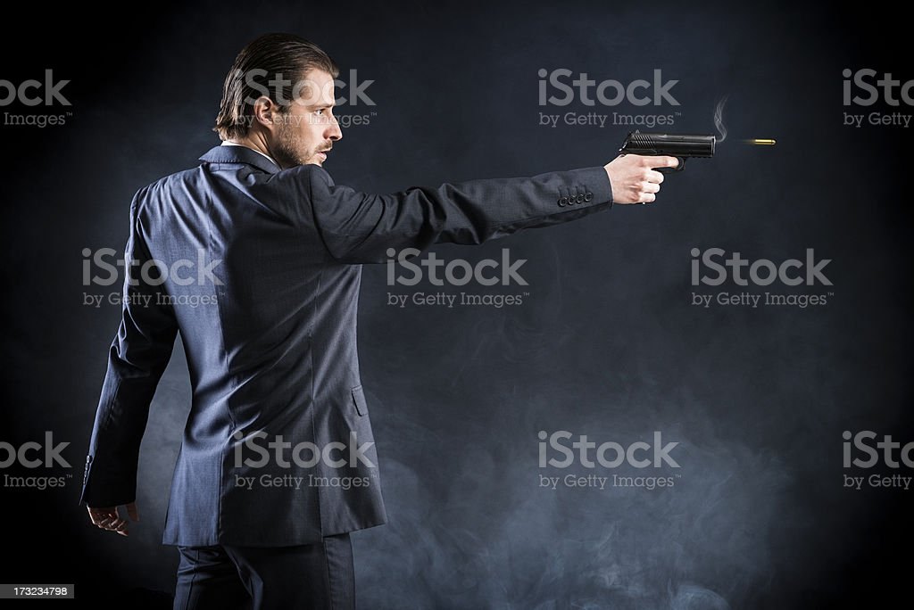 Assassin, gangster suit aiming with gun and fires, assassin, killer stock photo