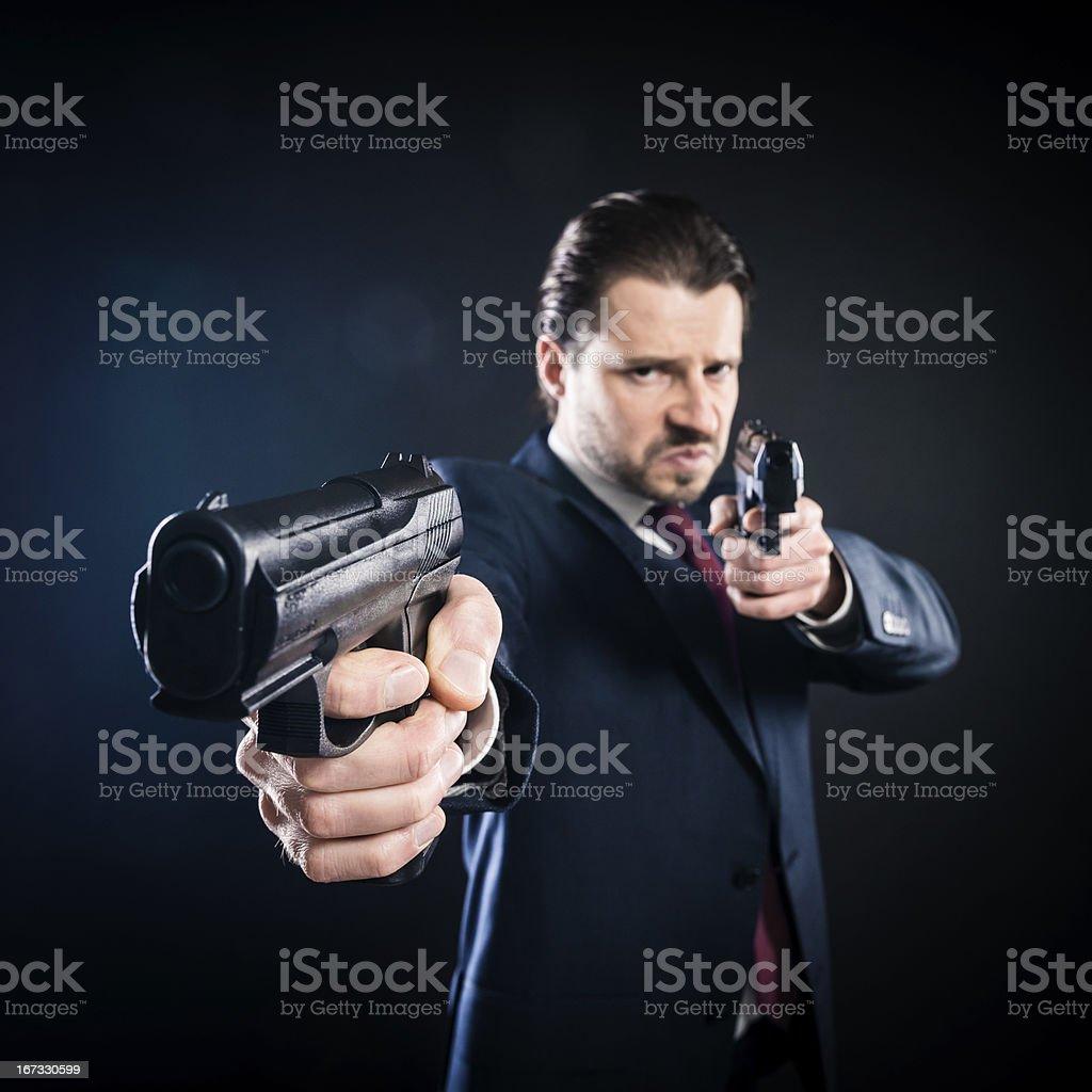 Assassin, gangster suit aiming with two guns, mafioso, killer, mafia stock photo
