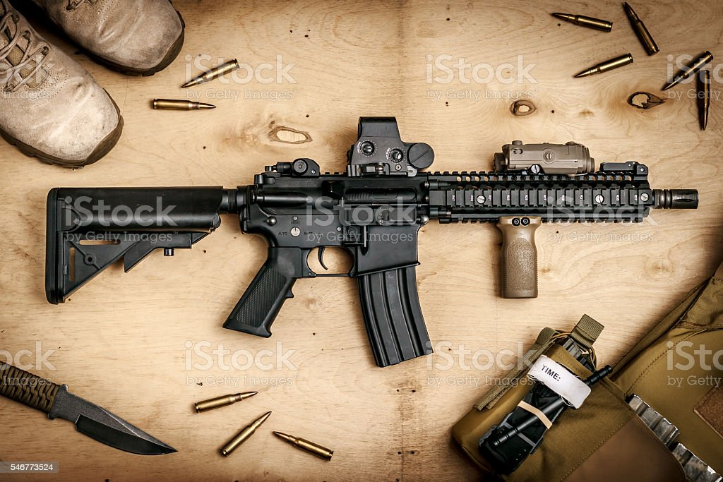 Assault rifle on a wooden table stock photo