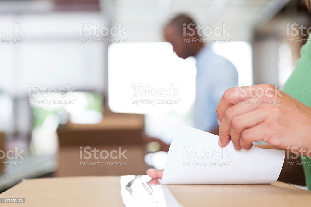 Assembly line worker in warehouse sticking label to package stock photo
