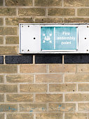 Assembly point sign on brick wall