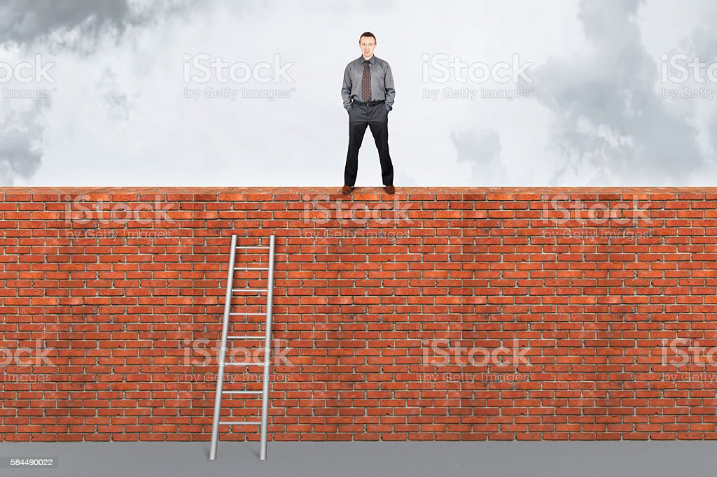 Assertive man stands on the top of a brick wall stock photo