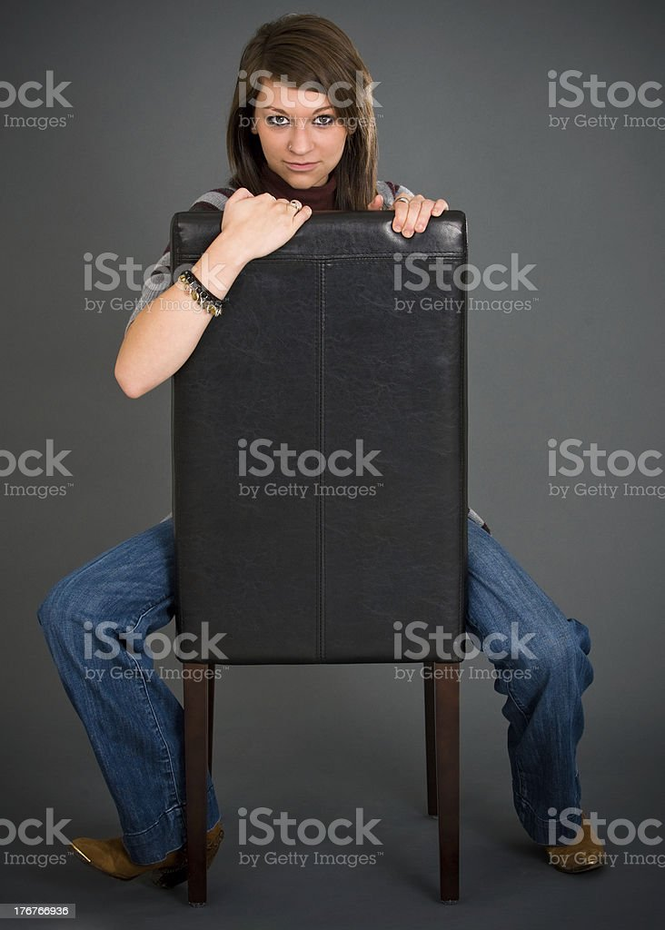 Assertive Young Woman Posed with Backwards Chair royalty-free stock photo