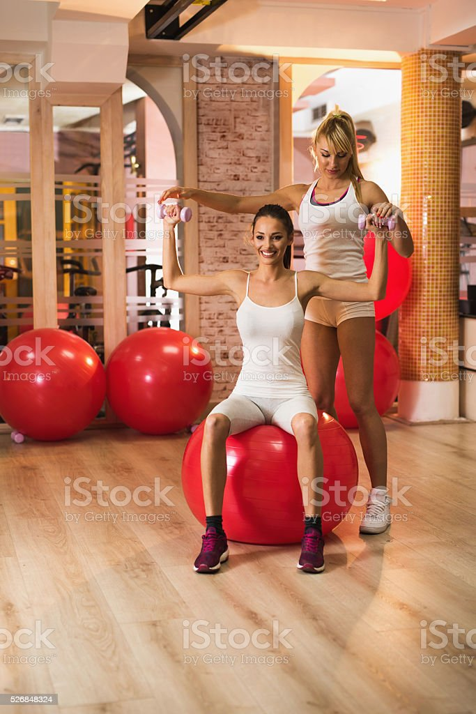Assistance in doing weight exercises on a fitness ball. stock photo