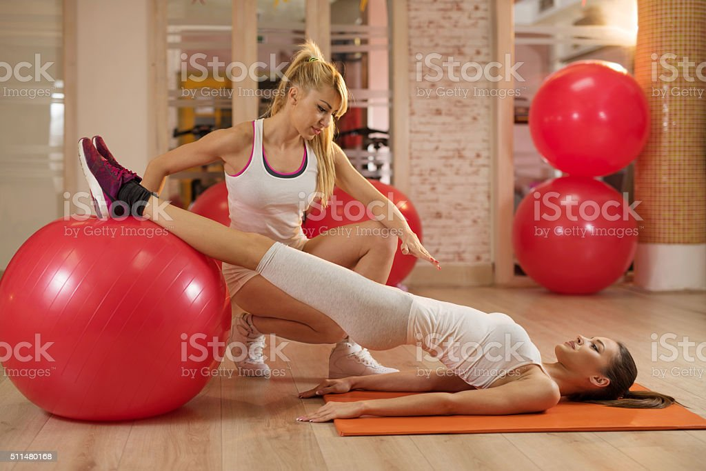 Assistance in Pilates exercises during training class. stock photo
