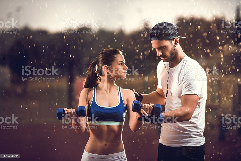 Assistance with dumbbell exercises on a rainy day. stock photo