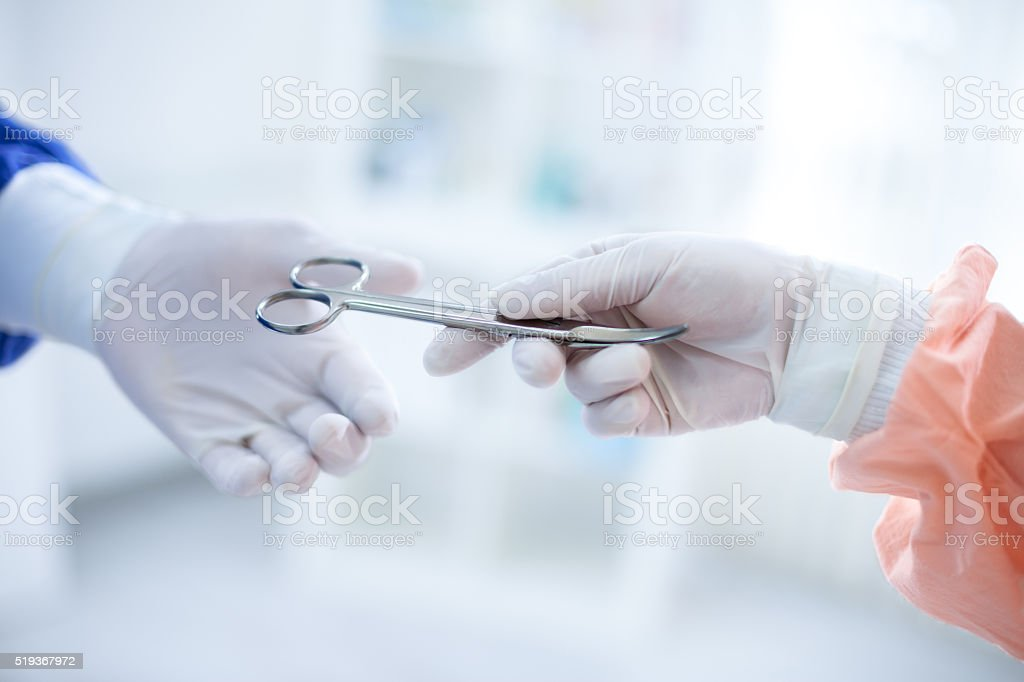 assistant adds instruments during surgery stock photo