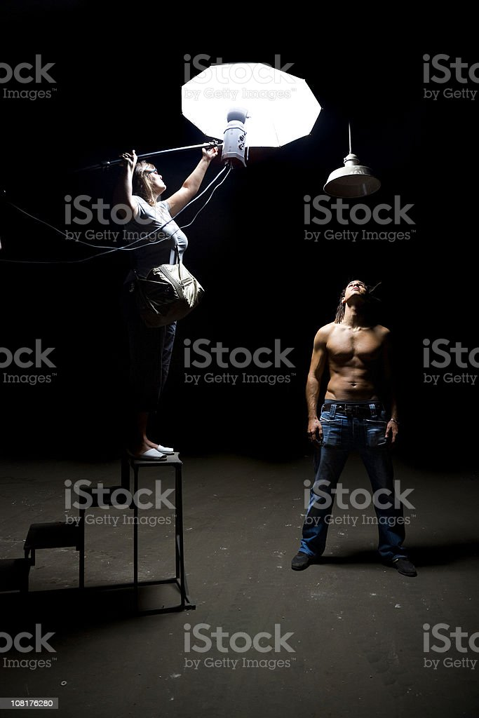 Assistant Holding Lights Above Male Model in Photograph Scene royalty-free stock photo