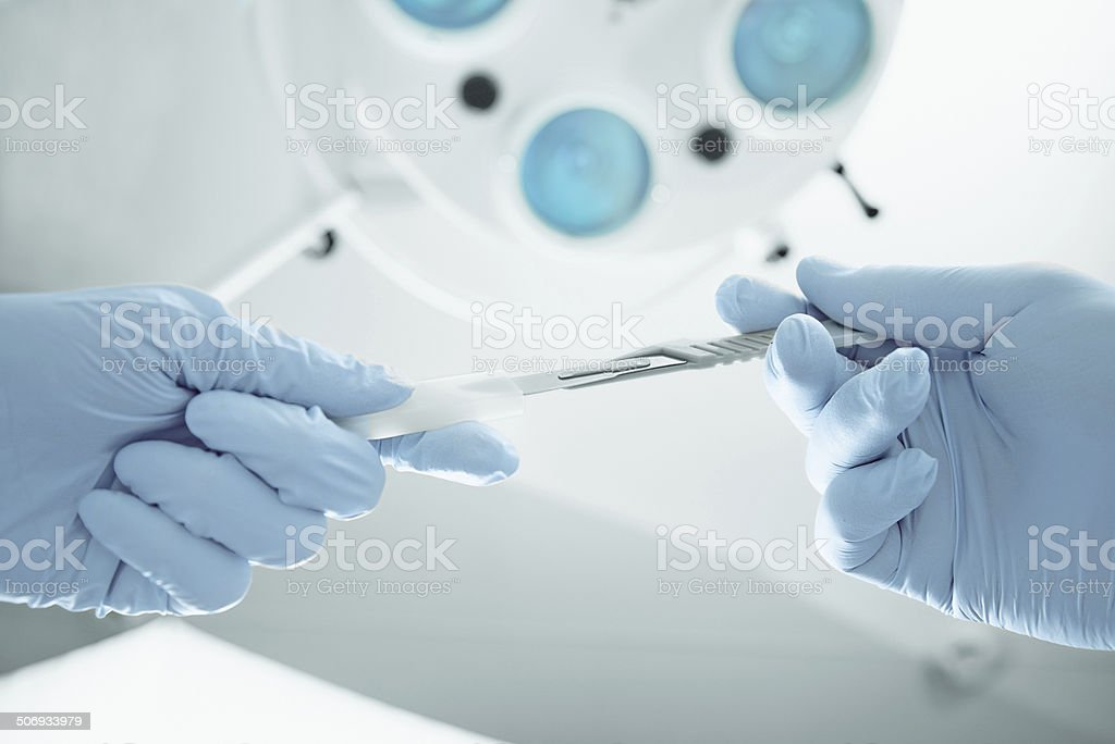 Assistant passes a scalpel to surgeon stock photo