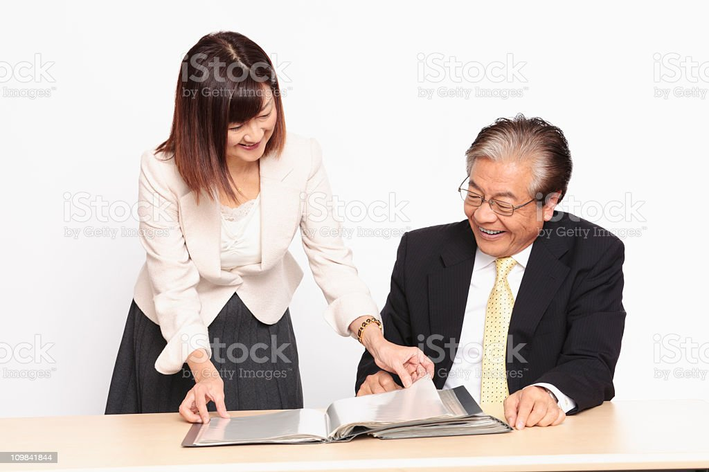 Assistant presenting books to the CEO, both smiling stock photo