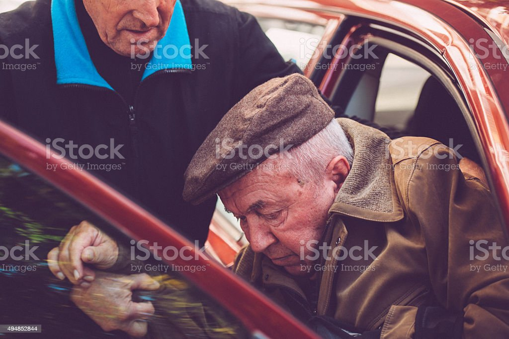 Assistent Helping Elderly Disabled Man to Leave the Car, Europe stock photo