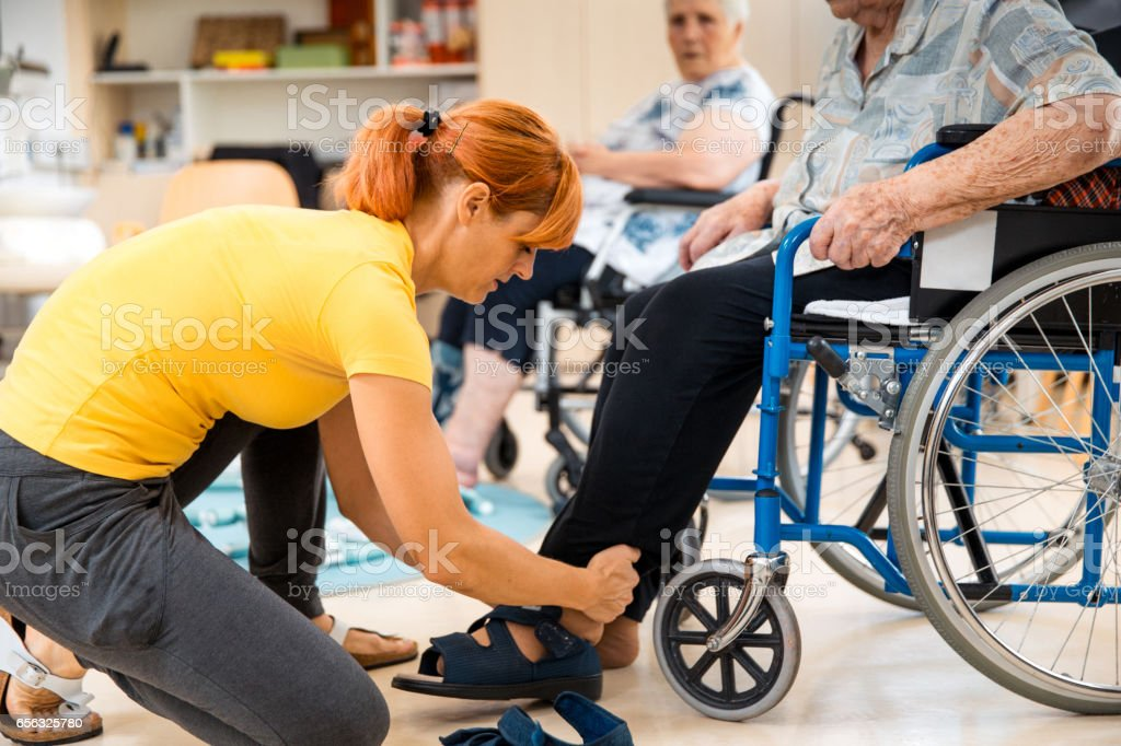 Assistent Helping Senior During Foot Massage In The Retirement Community stock photo