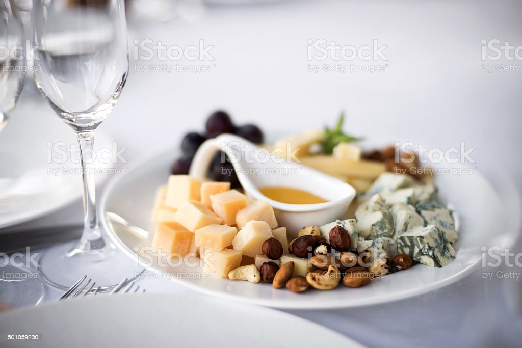 Assorted Cheeses with Grapes and Nuts on Platter stock photo
