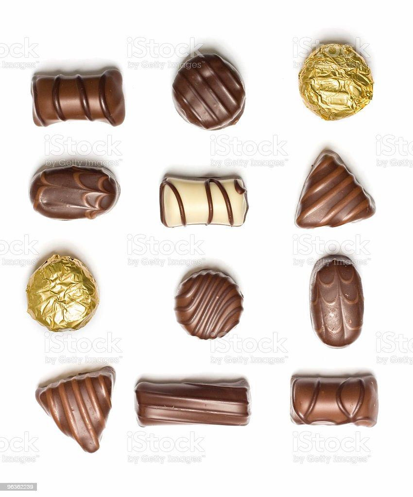 Assorted chocolates laid individually on white background stock photo