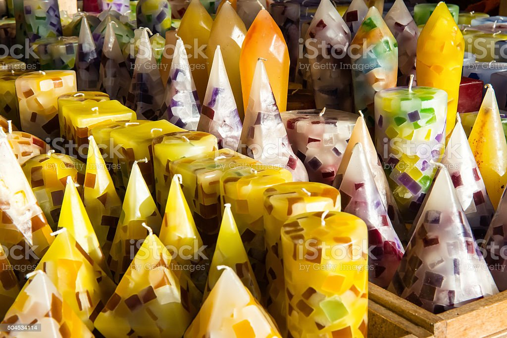 Assorted colorful yellow wax candles in a shop stock photo