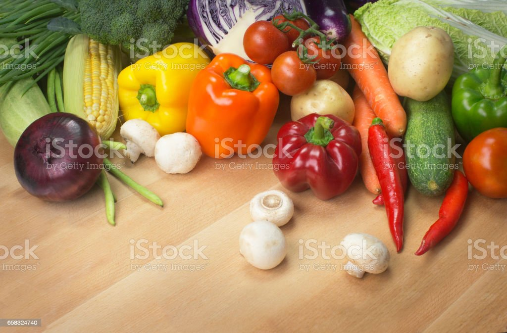 Assorted colourful vegetables on wooden table top. stock photo