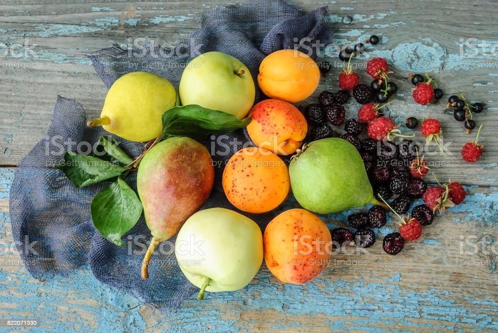 Assorted fresh fruits and berries on a wooden surface stock photo