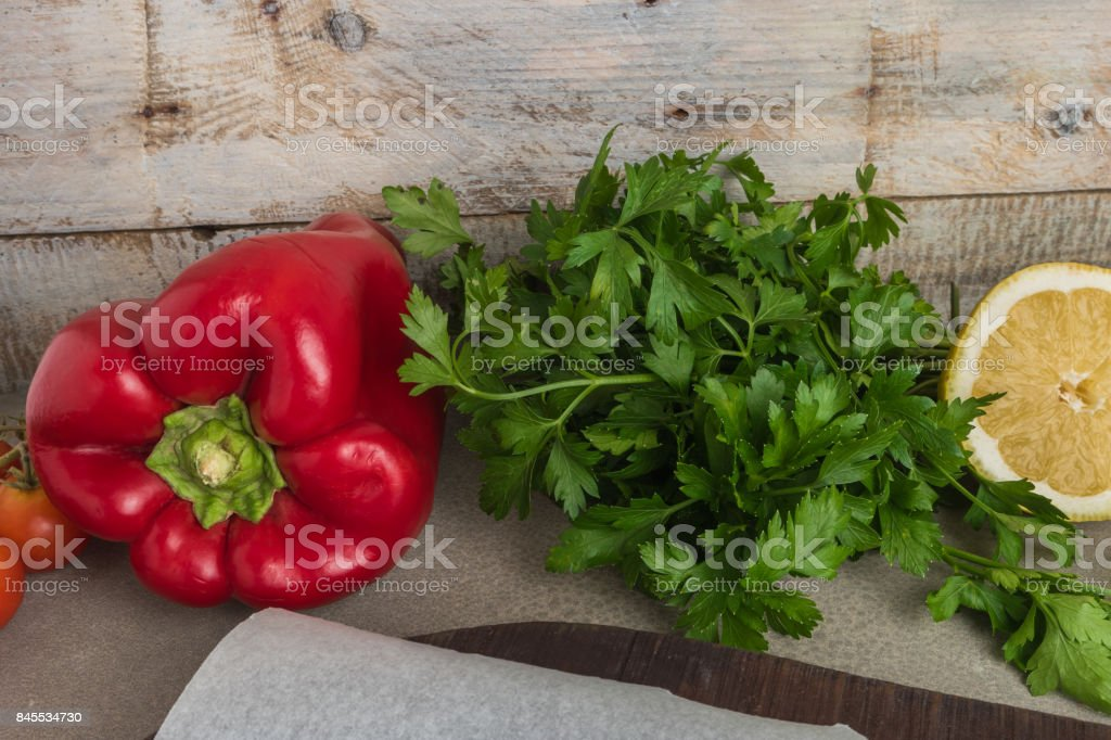 Assorted fresh healthy organic vegetables. Parsley, tomatoes red pepper and Lemon on top of wooden table. stock photo