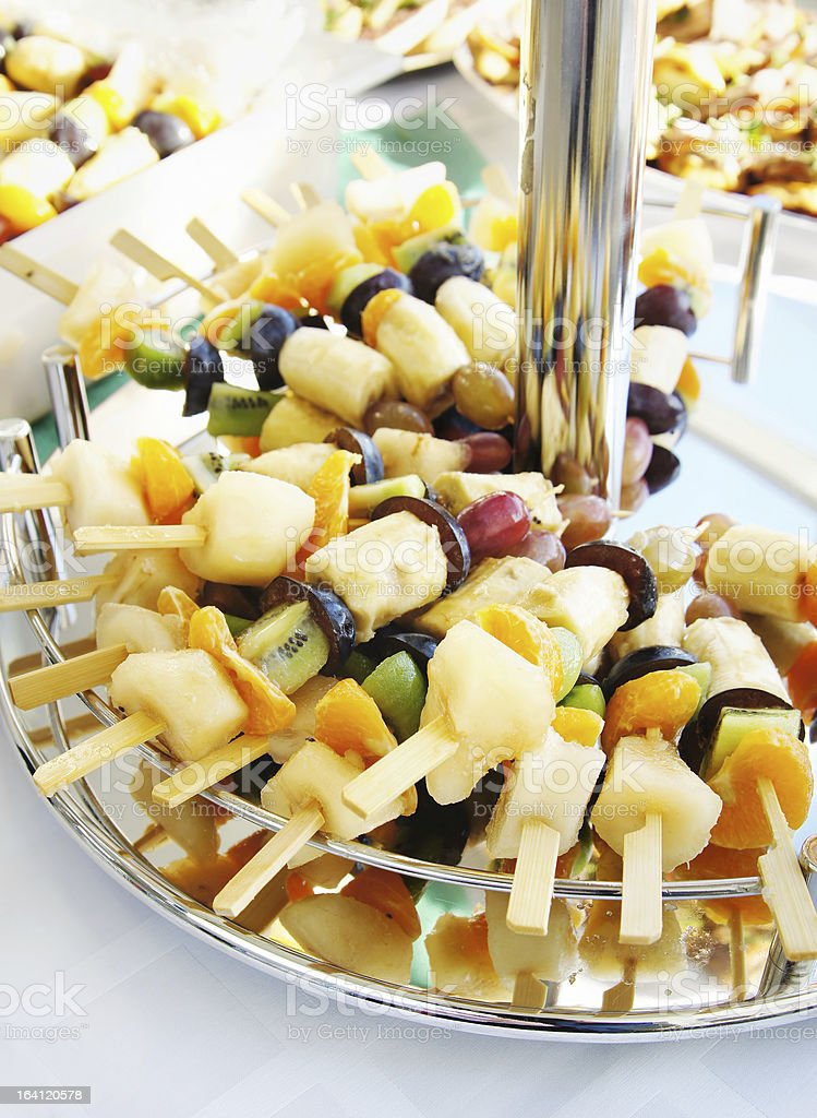 Assorted fruits at skewers on a stand royalty-free stock photo