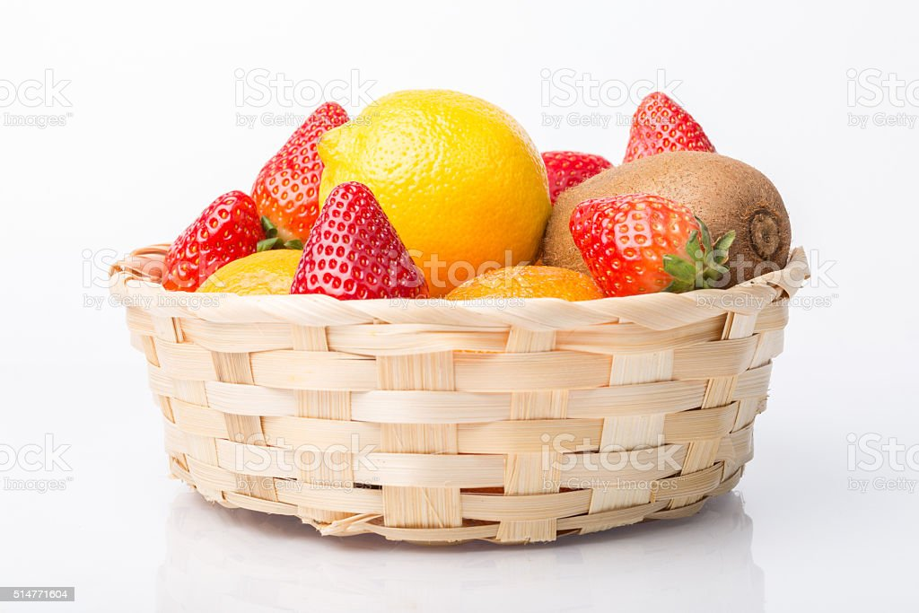Assorted fruits in wicker basket isolated on white stock photo
