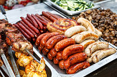 Assorted German sausages grilled in a steel container