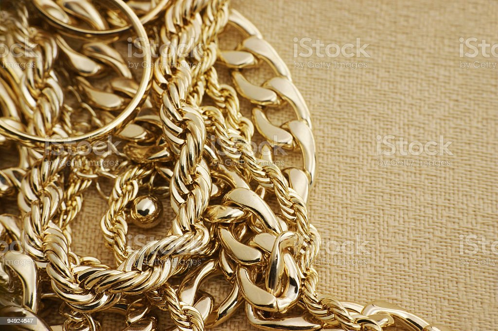 Assorted golden jewelry on brown material royalty-free stock photo