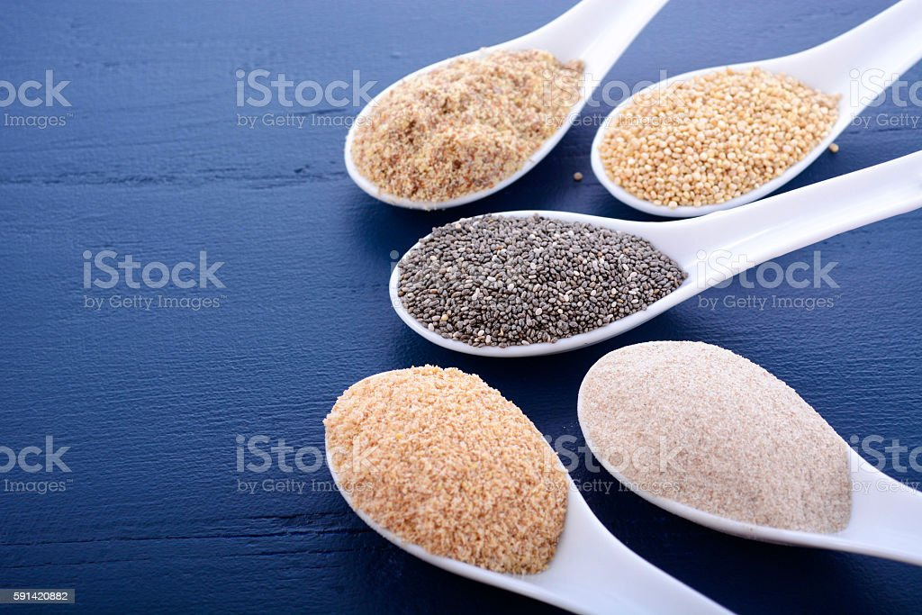 Assorted grains on dark wood table. stock photo