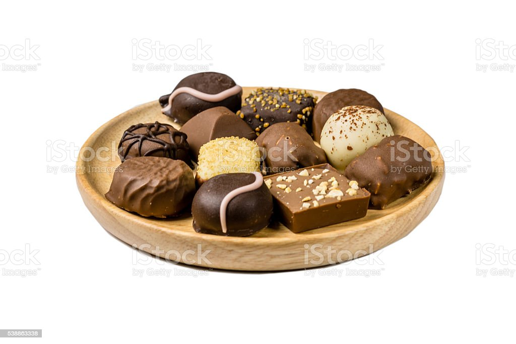 Assorted kind of chocolates on a wooden plate royalty-free stock photo