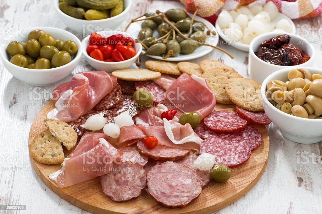 Assorted meat snacks, sausages and pickles on wooden board stock photo