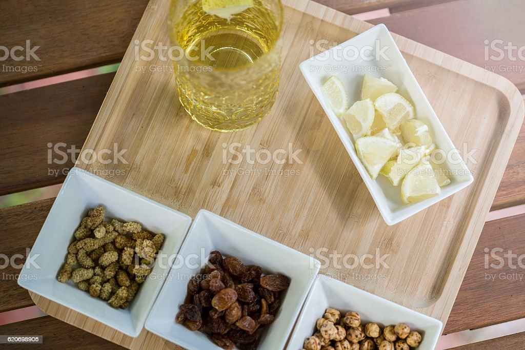 Assorted nuts in white bowl on wooden surface stock photo
