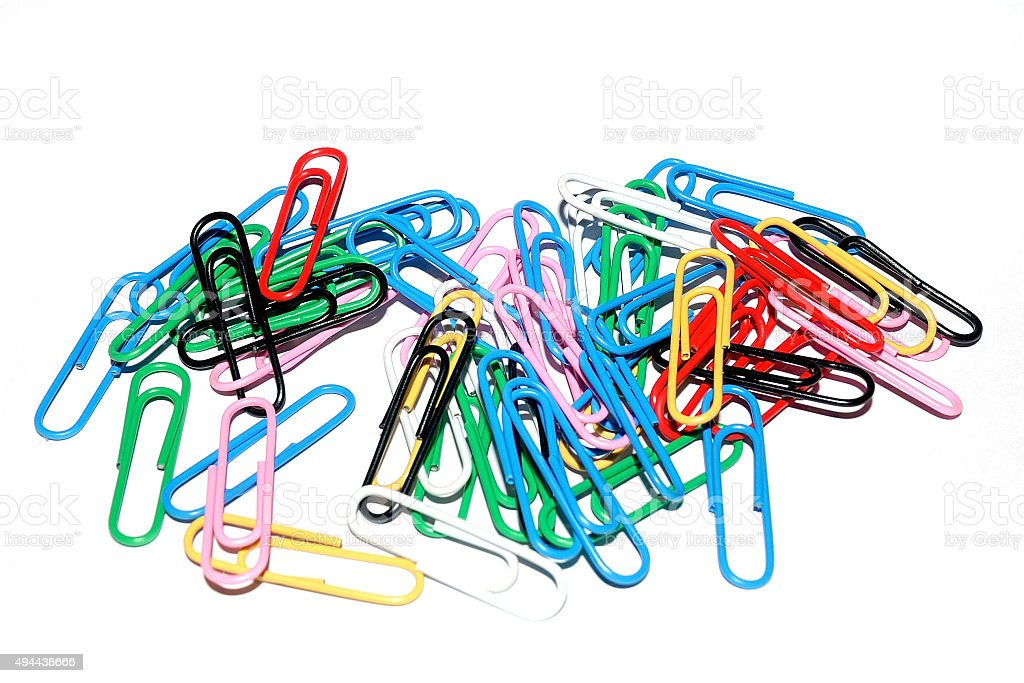 Assorted paper clips are laying on a white background stock photo