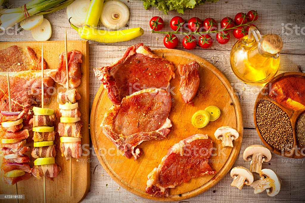 Assorted raw meats and vegetables on skewers and platters stock photo