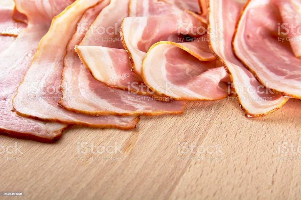 Assorted slices of fat pink bacon on wooden desk stock photo