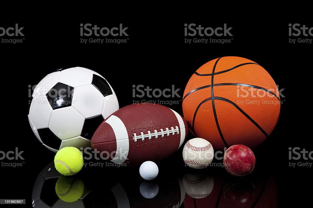 Assorted sports balls on a black background stock photo