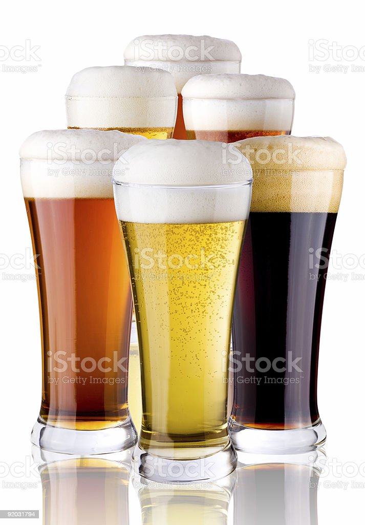 Assorted tall glasses with beer and foam on top royalty-free stock photo