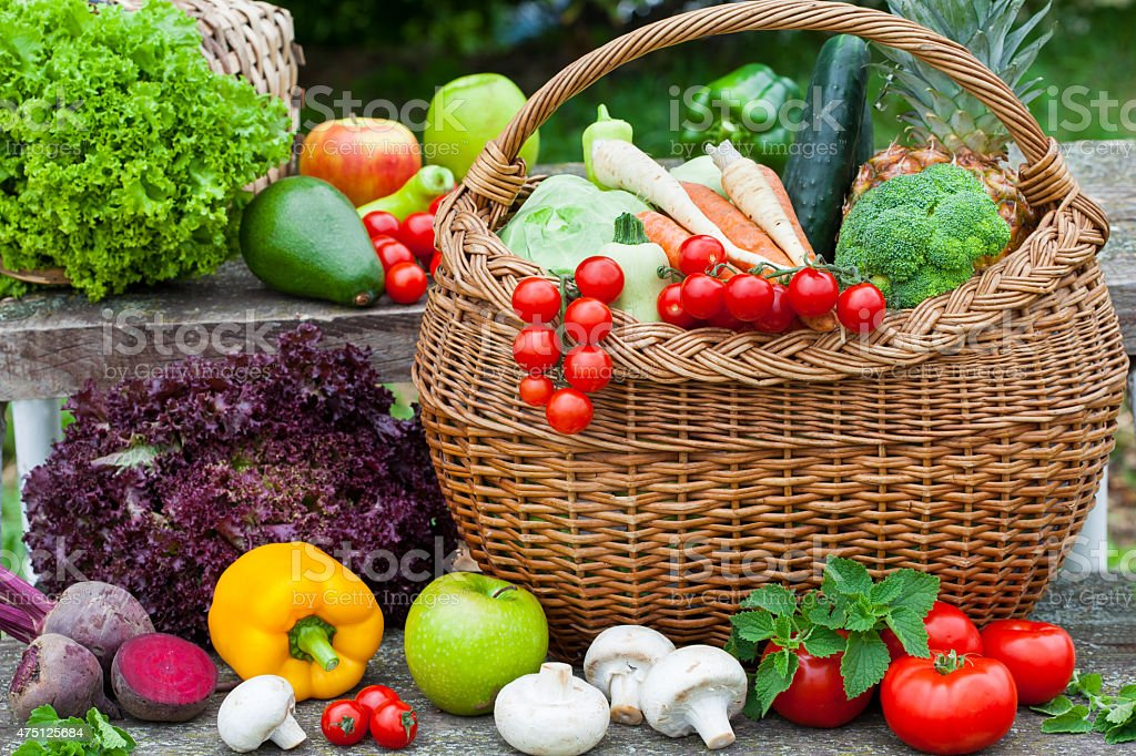 Assorted vegetables in wicker basket stock photo