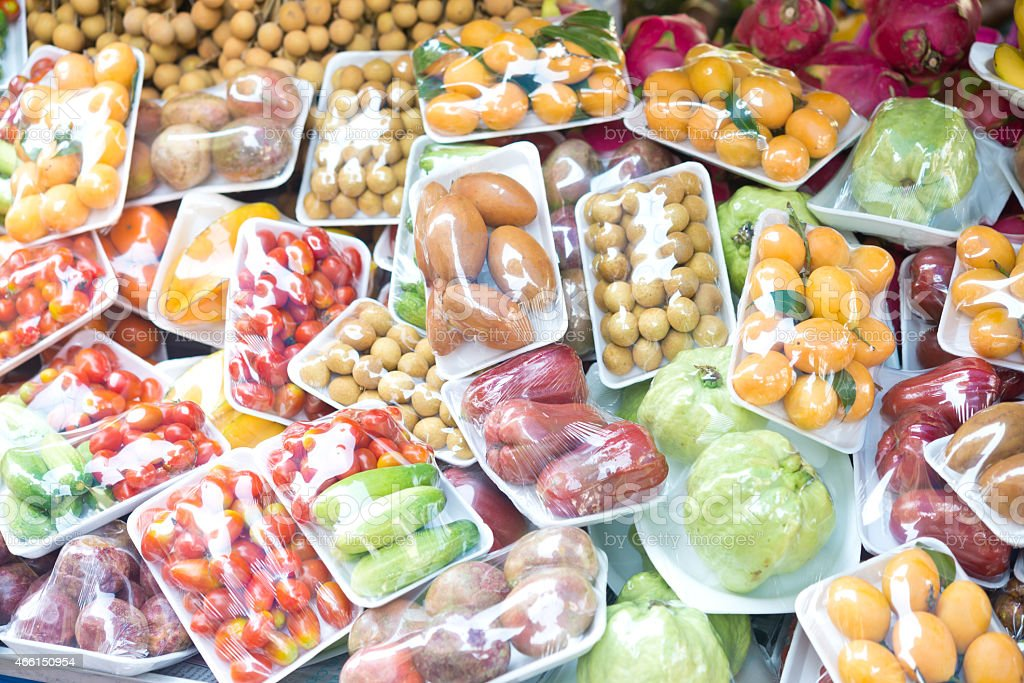 Assorted wrapped packages of various fruits and vegetables stock photo