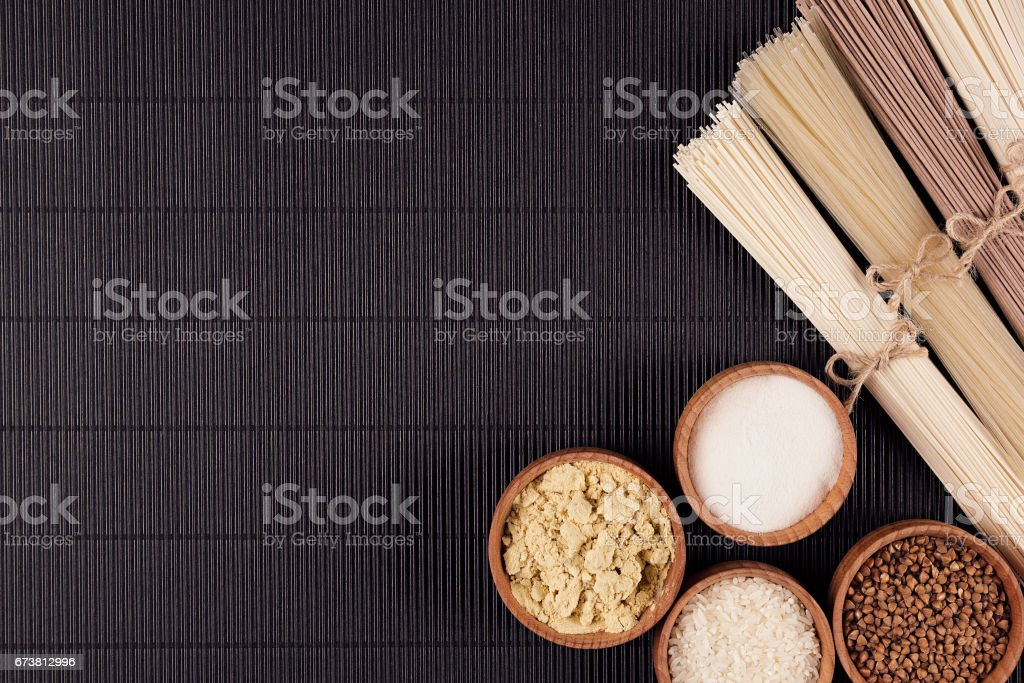 Assortmen of bundles raw noodles with ingredient in wooden bowls on black striped mat background with copy space, top view. stock photo
